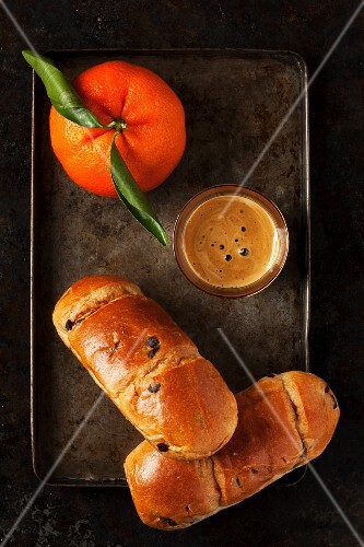 Chocolate brioche rolls, an espresso and a mandarin on a baking tray