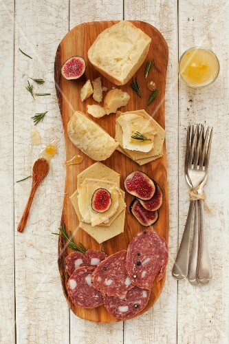A platter of cheese and cured meats with crackers, honey and figs