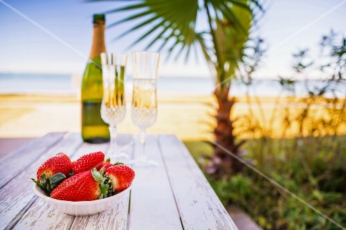 A bowl of strawberries and champagne on a beach