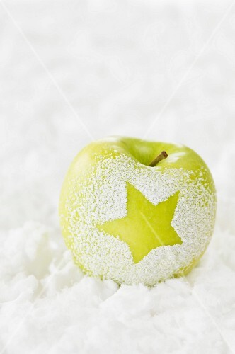 An apple in the snow decorated with a star
