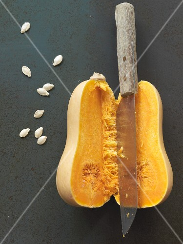 A halved butternut squash with a knife and seeds