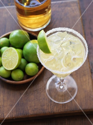 A margarita with a salted rim garnished with a wedge of lime