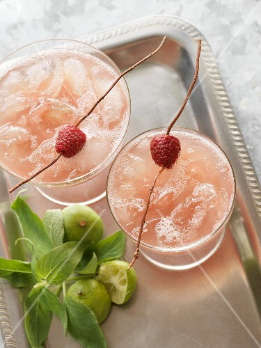 Raspberry margaritas next to halved limes and mint leaves