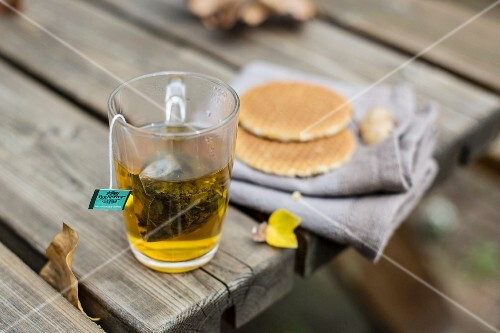 A cup of tea and syrup waffles on a wooden table in a garden