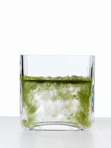 Water with herb powder in a thick glass
