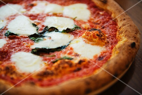 A Margherita pizza on a wooden table (close-up)