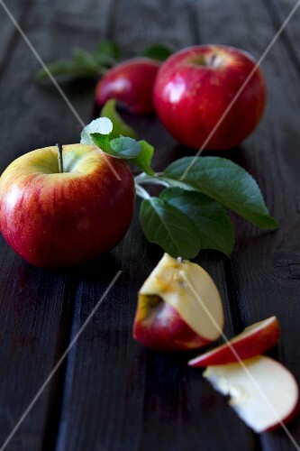 Apples with leaves, whole and chopped, on a wooden surface