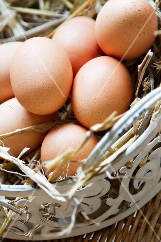 Brown eggs in a white metal basket filled with straw