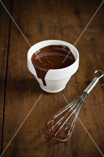 Chocolate sauce in a bowl and on a whisk on a wooden surface