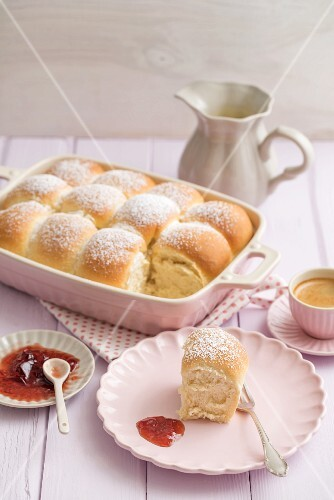 Buchteln (baked, sweet yeast dumplings) with vanilla sauce, strawberry jam and coffee