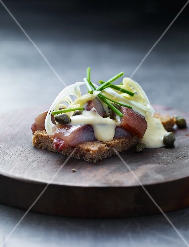 A slice of bread topped with herring, remoulade and capers
