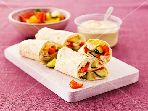 Wraps with hummus, courgette and peppers on a board