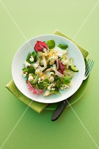 A mixed leaf salad with popcorn, turkey ham, artichokes and egg