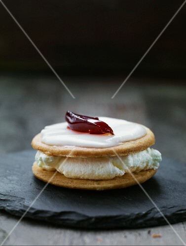 A sandwich biscuit filled with cream and topped with lemon glaze and raspberry jelly