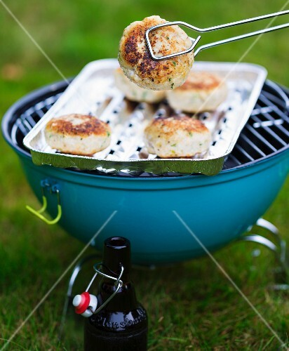Fish cakes with coriander on an aluminium tray on a barbecue