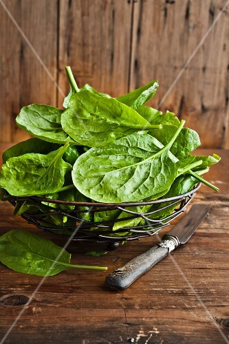 Fresh spinach in a metal basket on a wooden surface