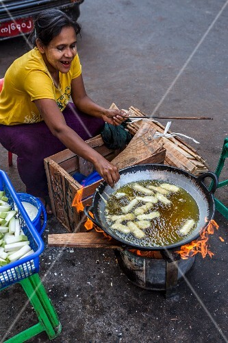 A woman frying vegetables at a market in Myanmar