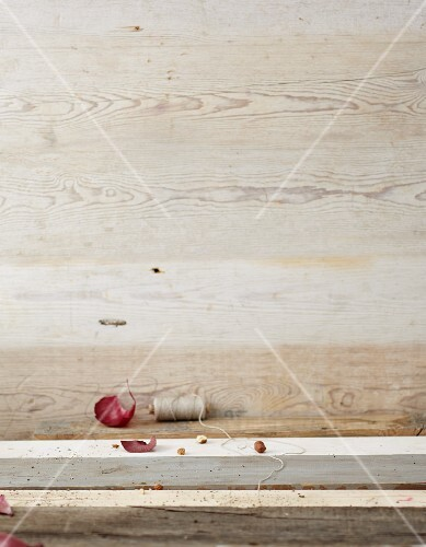 Red onion skin and kitchen twine on a wooden surface