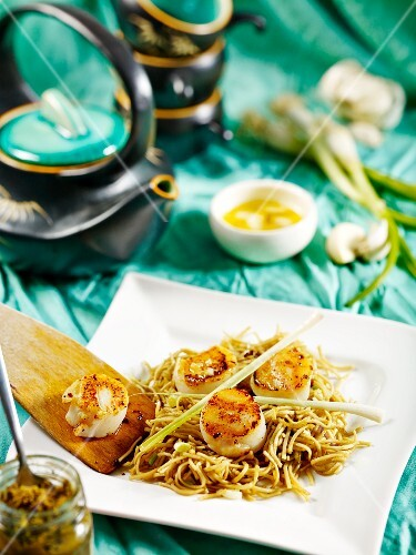 Fried scallops on wheat noodles with green curry paste, garlic butter and spring onions (Japan)