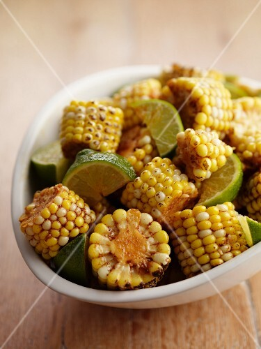 Grilled corn cobs with lime wedges