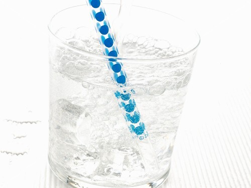 A glass of sparkling mineral water with ice cubes and a straw