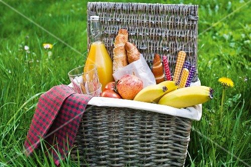 A picnic basket filled with fruit, rolls and orange juice