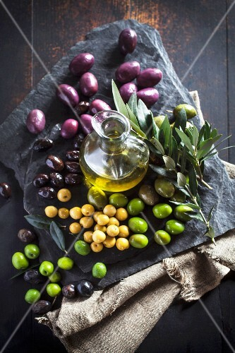 A carafe of olive oil, various olives and an olive spring on a stone platter