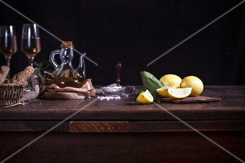 Lemons, olive oil and white wine on a wooden table