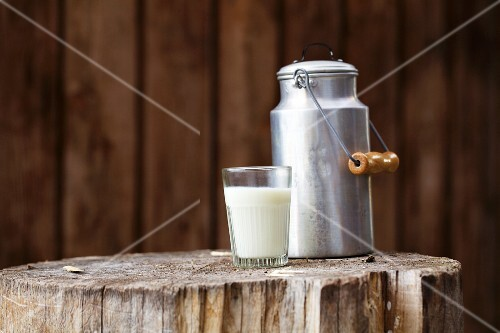 A glass of milk with a milk churn