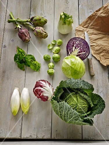 Various types of vegetables on a wooden surface (artichokes, fennel, cabbages, radicchio, chicory and winter spinach)