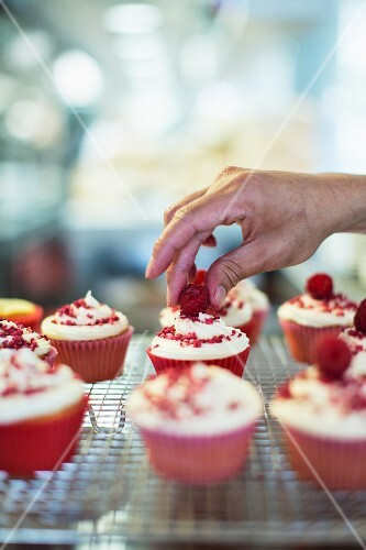 Red Velvet cupcakes being decorated with raspberries