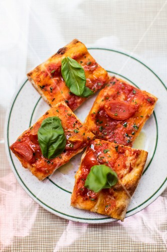 Small slices of pizza with tomatoes and basil