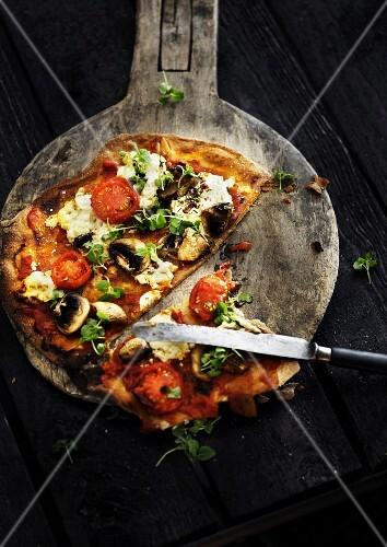 A sliced vegetarian pizza on a wooden pizza paddle