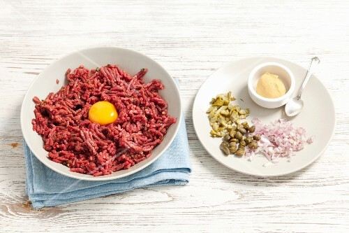 Ingredients for a hamburger: minced meat with egg yolk, onions, cornichons, capers and mustard