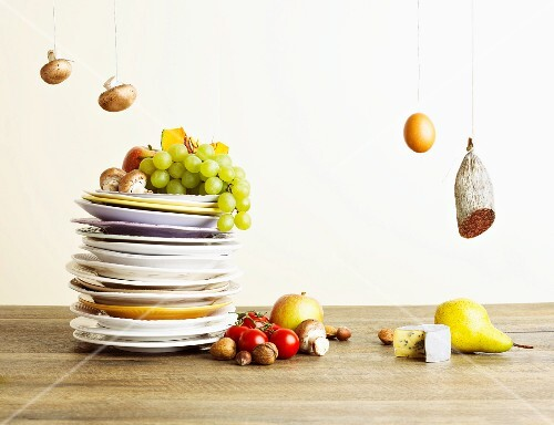 A stack of plates with fruit, vegetables and mushrooms next to an egg, salami and cheese