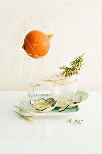 An arrangement of pumpkin and rosemary on crockery