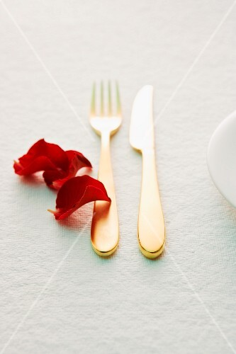 Golden cutlery and red rose petals