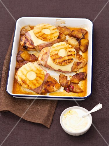 Baked chicken breasts wrapped in ham topped with cheese and pineapple