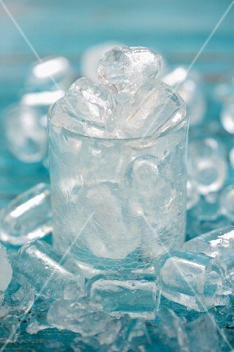 Ice cubes in a glass and around it