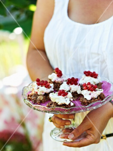 Chocolate crispy cakes topped with cream and redcurrants