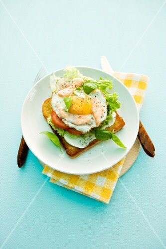 A slice of toast topped with a fried egg and salmon