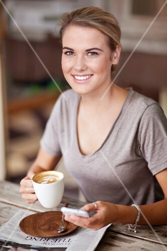 A young woman with a cappuccino, mobile phone and a daily newspaper