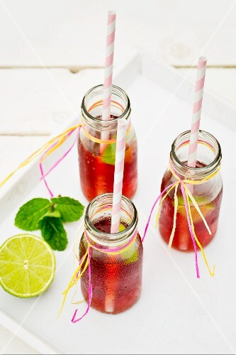 Three small bottles of iced tea with lime and peppermint on a white tray