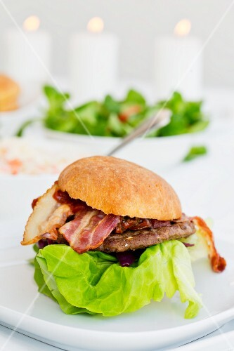 A hamburger with bacon and lettuce