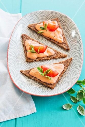 Bread triangles topped with ricotta and tomato cream and basil