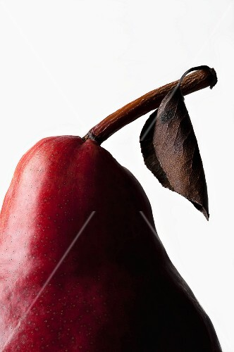 Detail of a red pear with a stem and a leaf