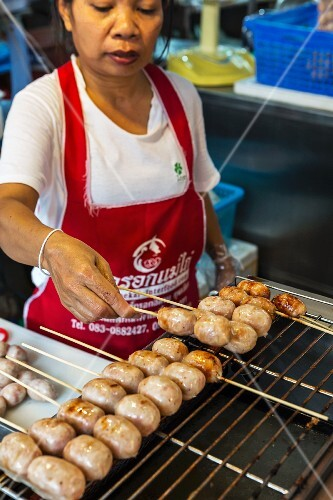 A woman grilling Thai sausages