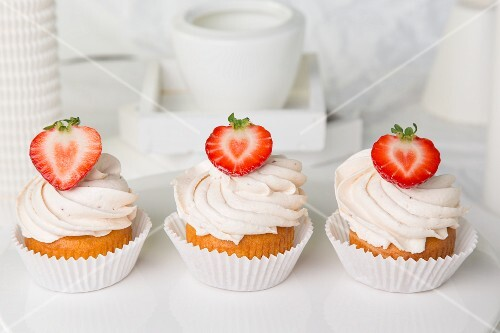 Three strawberry cupcakes topped with buttercream