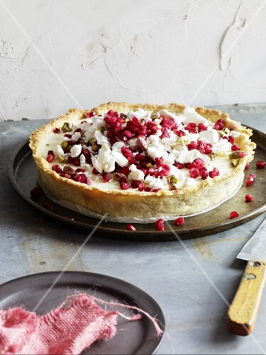 An ice cold lemon pie with pomegranate seeds