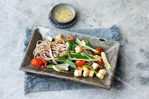 Oriental noodles with tofu, mange tout and tomatoes
